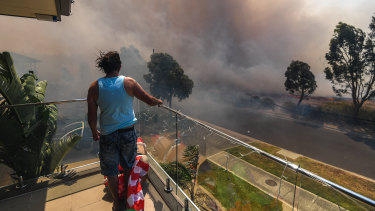 Ange Vlahopoulos watches as the fire approaches his home at 4pm today.