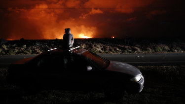 Brittany Kimball watches as lava erupts from a fissure near Pahoa, Hawaii, on Saturday.