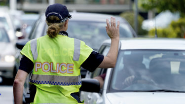 A police officer stops a driver at a checkpoint at Coolangatta on the Queensland - New South Wales border on Thursday.