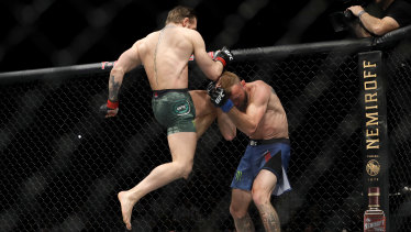 Ducking for cover: Donald Cerrone on the defensive as Conor McGregor launches into an attack.