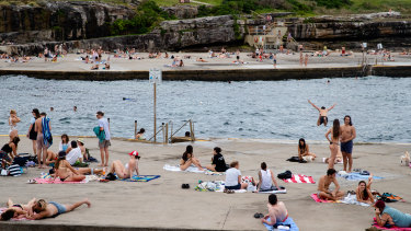 People enjoying the warm day at Clovelly on Monday. The NSW government launched its COVID-19 summer plan on Monday.