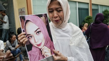 Mrs Nuke (who gave only one name) holds a picture of her daughter, Puspita Eka Putri, who was aboard the crashed Lion Air passenger flight JT610.