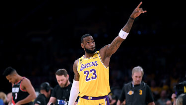 LeBron James #23 of the Los Angeles Lakers points at the two retired jerseys in the rafters to honour Kobe Bryant before the game against the Portland Trail Blazers,