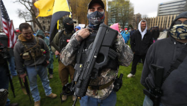 A protester shows off his powerful gun as demonstrators swarmed the State Capitol in Lansing, Michigan.