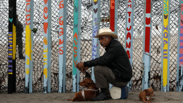 A local resident sits with his dogs in front of the US border fence at the beach in Tijuana, Mexico.