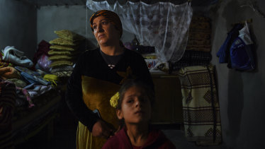 Sehla (left) complains that the roof of her hut leaks as she plaits her daughters hair in Basirma refugee camp, Iraq.
