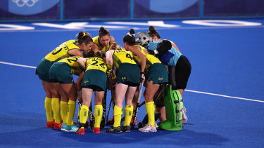 Australia players huddle on pitch during the Women's Preliminary Pool B match between New Zealand and Australia.
