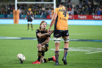Damian McKenzie shakes the hand of Darcy Swain after the Brumbies lock was yellow carded.