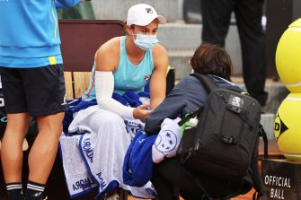 Ash Barty speaks to a trainer before retiring hurt in Rome.