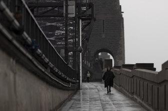A man walks across the Sydney Harbour Bridge under heavy rain yesterday.