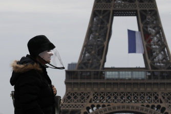 A resident wears a protective mask near the Eiffel Tower.