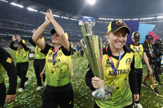 Alyssa Healy celebrates with the World Cup trophy in 2020.