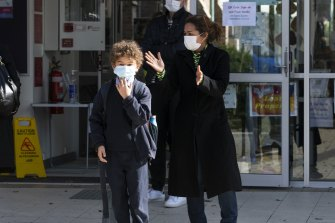 Isabel Batson collects her son from St Charles' Primary School in Waverley after a child tested positive to COVID-19 on Tuesday.