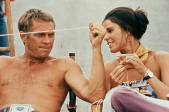 A shirtless Steve McQueen sitting next to Ali MacGraw on the set of the film 'The Getaway', 1972.