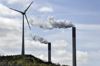 Chimneys of a coal-fired power plant smoke beside a wind turbine in Gelsenkirchen, Germany.