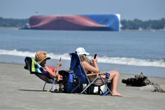 Beachgoers relax on Jekyll Island's Driftwood Beach as the Golden Ray cargo ship is capsized in the background.