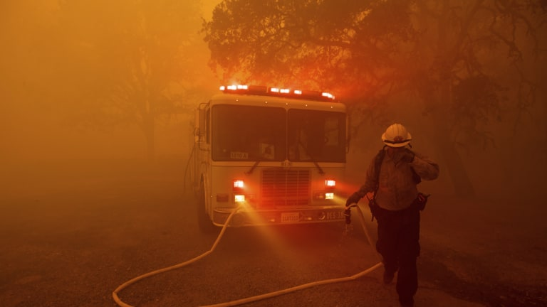 A firefighter rushes to save a home as the River Fire tears through Lakeport, California, on Tuesday.