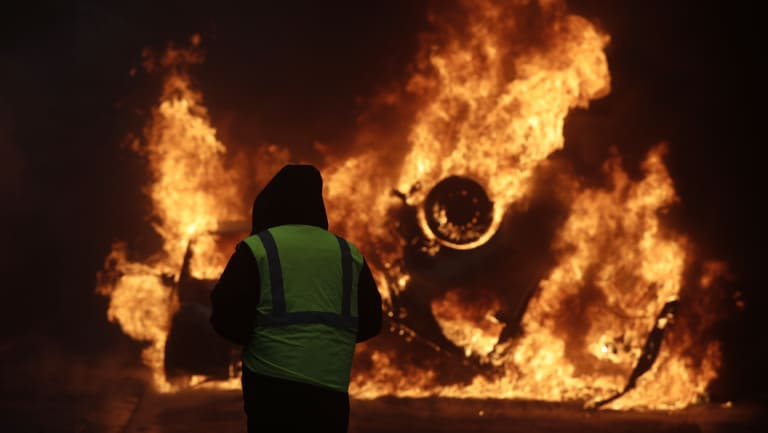 A demonstrator watches a burning car near the Champs-Elysees during a demonstration on Saturday.