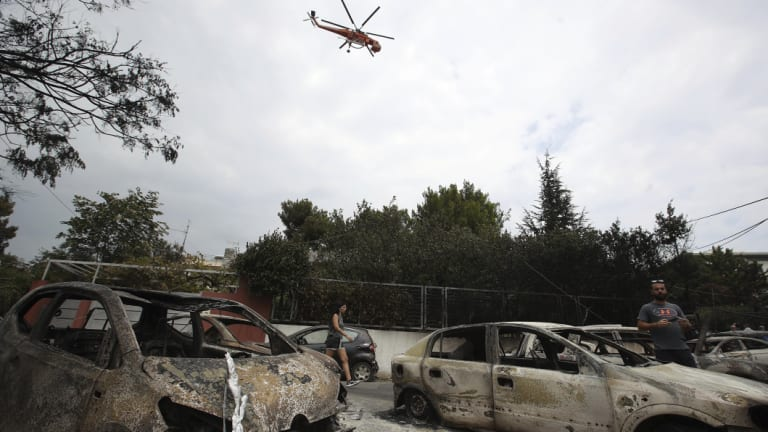 A firefighting helicopter flies above burnt-out cars in Mati, east of Athens.