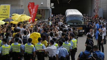 Supporters gather as photographers scramble around a prison van carrying Occupy Central leaders Chan Kin-man, Benny Tai, Raphael Wong and Shiu Ka-chun at a court in Hong Kong.