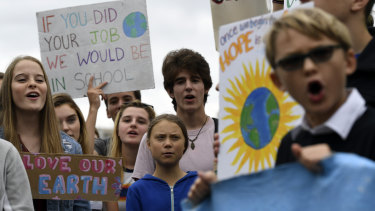 Greta Thunberg, centre in blue, joins other young climate activists Friday for a climate strike outside the White House in Washington on Friday.