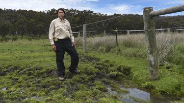 HeliSurveys chief pilot Colin de Pagter stands over a damaged section of grassland.