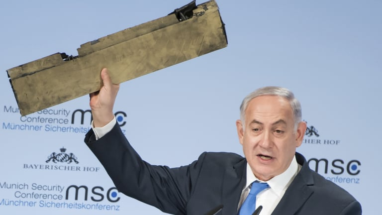 Israeli Prime Minister Benjamin Netanyahu holds part of a downed drone during his speech at the Munich Security Conference.