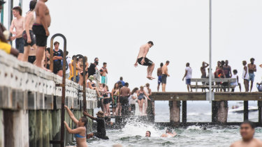 Thrill seekers take a plunge off Frankston pier after high temperatures earlier this week.