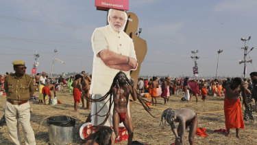 A policeman stands next to a cut out photograph of Indian Prime Minister Narendra Modi as Hindu holy men participate in a ritual after a holy dip at Sangam, the confluence of sacred rivers the Yamuna, the Ganges and the mythical Saraswat in India.