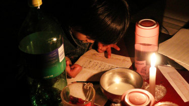 Xu Yuanyuan, then 7, does her maths homework by candlelight in Picun Village, Beijing.
