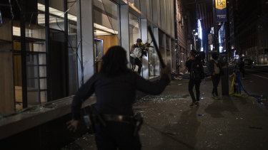 New York police run towards people as they jump out of a store with items they took hours after a solidarity rally.