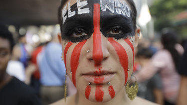 """A woman poses for a photo with the words """"Not him"""" written in Portuguese on her face during a protest against Jair Bolsonaro, a far-right presidential candidate in Sao Paulo."""