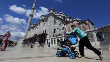 A Syrian boy pushes a pram past Fatih mosque in Istanbul. Syrians say Turkey has been detaining and forcing some refugees to return home in the past month.