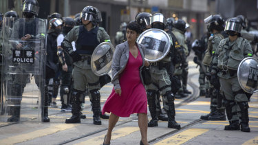 A woman walks past Hong Kong riot police clearing up a road in the Central district of Hong Kong on Friday.