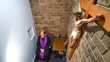 Father Nicholas Pearce in the confessional at Holy Family Church in  Mount Waverley.