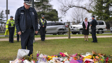 Graham Ashton, Chief Commissioner of Victoria Police, lays flowers at the make shift memorial where Eurydice Dixon's body was found at the Princes Park, North Carlton. 18 June 2018. The Age News.