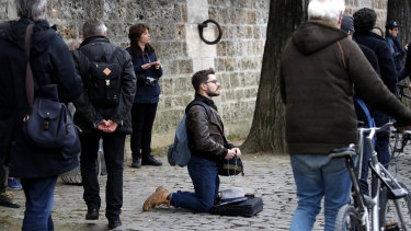 A man kneels as people watch and photograph the Notre Dame cathedral after the fire in Paris.