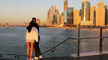Tourists look at the skyline at sunset, in Dubai. With peak tourism season in full swing, coronavirus infections are surging to unprecedented heights, with daily case counts nearly tripling in the past month.