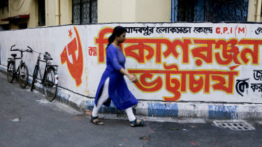A woman walks past graffiti in Kolkata for the Communist Party of India-Marxist. India's general elections will be held in seven phases from April 11 to May 19.