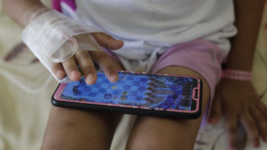 A young dengue patient plays with a smartphone at the San Lazaro government hospital in Manila.