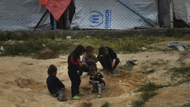 Disease trap: Children play in the dirt near the fence line of the foreign ISIS section of Al Hawl camp in Syria.