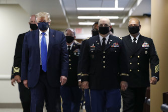 President Donald Trump with men in black masks.