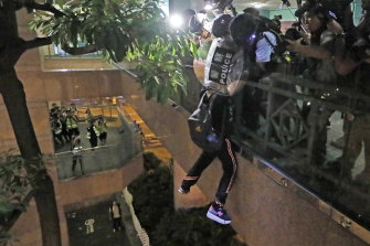 A protester hangs from a bridge as police officers try to pull him up after a scuffle with police.