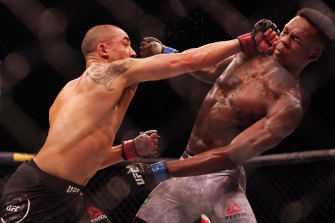 Robert Whittaker (left) got some hits in before his defeat to Israel Adesanya (right).