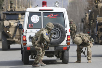 British soldiers with NATO-led Resolute Support Mission check an ambulance at the site of the attack.
