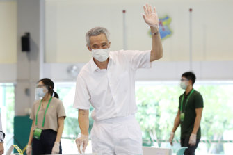 Singapore Prime Minister Lee Hsien Loong waves as he casts his vote on Friday.