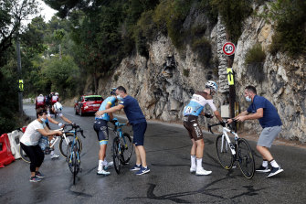 France's Pierre Latour, right, and Spain's Omar Fraile, left, are helped after falling during the first stage of the Tour de France cycling race over 156 kilometers (97 miles) with start and finish in Nice, southern France, Saturday, Aug. 29, 2020.