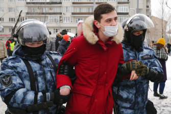 Police officers in Moscow detain a man during a protest against the jailing of opposition leader Alexei Navalny.