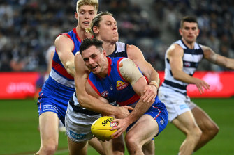 Toby McLean is tackled by Mark Blicavs.