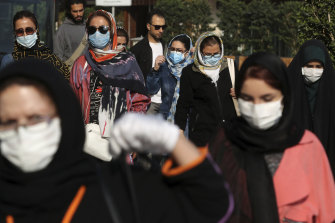 People wear protective face masks to help prevent the spread of the coronavirus in downtown Tehran, Iran, on Sunday, October 11.